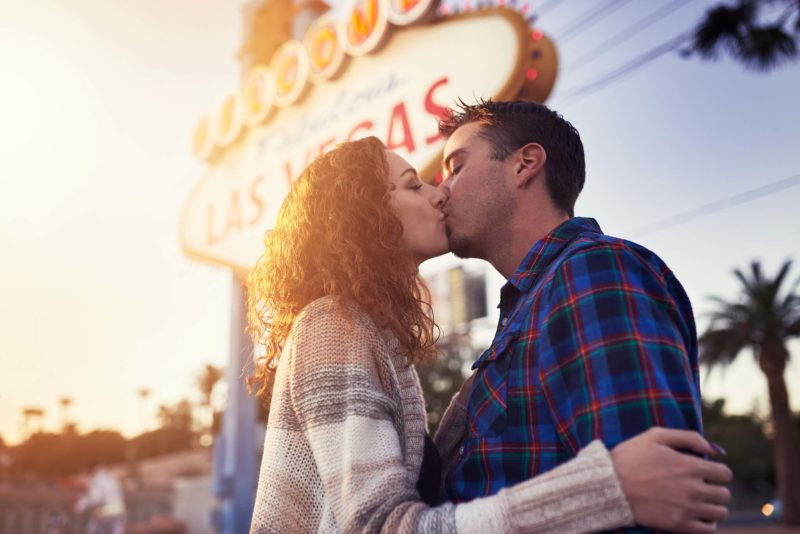 Romantic couple kissing in front of vegas sign